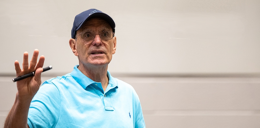 Dr Zirkel, wearing a blue polo shirt and blue baseball cap, gestures with a pen in his hand.