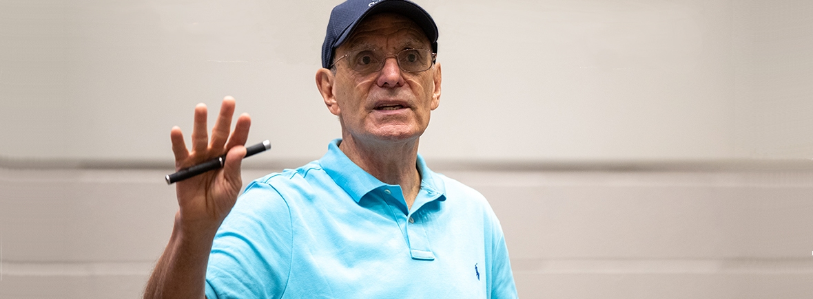 Photo of Perry Zirkel, lecturing in a blue baseball cap, blue collared shirt, holding a pen.