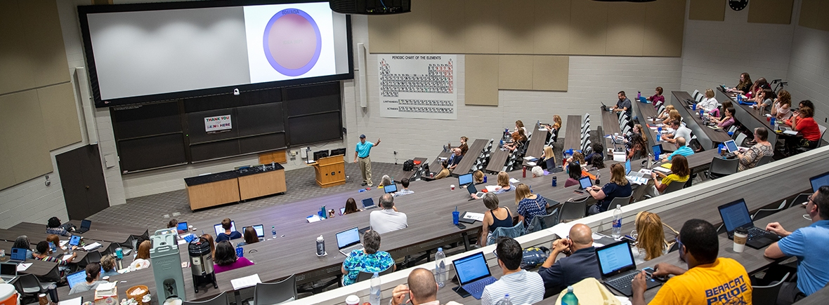 Photo of a large lecture hall at a university with attendees sitting at tiered desks and Zirkel giving a lecture before a screen at the front of the room.